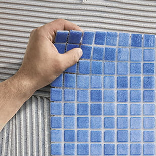 2. Place the mesh-mounted mosaics on top of the cement and press them down with a rubber trowel to guarantee an even surface.